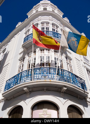 A Spanish flag, left, and a flag of the Canary Islands, right, wave in front of a building at Santa Cruz, La Palma, - Stock Photo