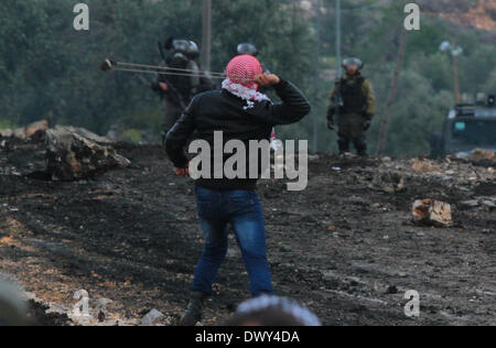 Nablus, West Bank, Palestinian Territory. 14th March 2014. A Palestinian hurls stones at Israeli soldiers during - Stock Photo