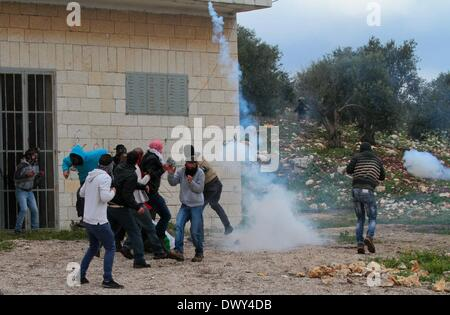 Nablus, West Bank, Palestinian Territory. 14th March 2014. Palestinians run to take cover from gas fired by Israeli - Stock Photo