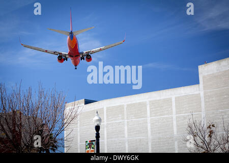 Southwest airliner flying a low flight pattern over Little Italy, approaching San Diego's airport Lindbergh Field, - Stock Photo