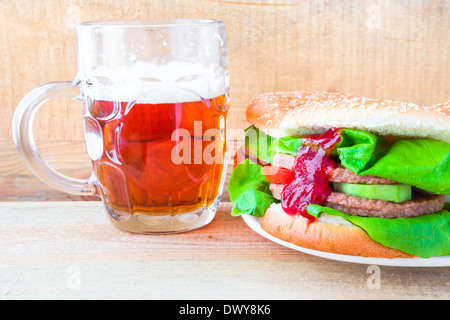 A delicious beef hamburger with a mug of beer - Stock Photo