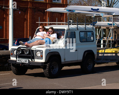 Two teenage girls sat on the bonnet of a Land Rover in the sunshine, Bideford, Devon, UK - Stock Photo