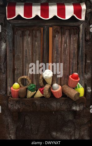 Various fake cupcakes, candy, doughnuts, and ice cream cones decoration on wooden window ledge. - Stock Photo