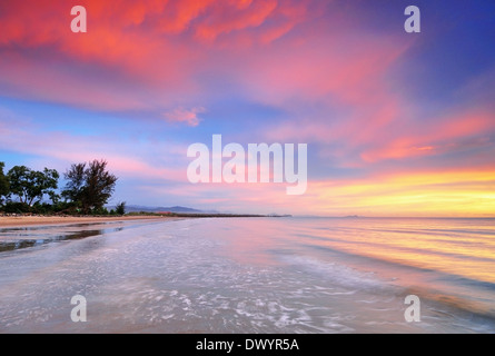 Tropical sunset and waves at the beach in Kota Kinabalu, Sabah, Borneo, Malaysia. - Stock Photo