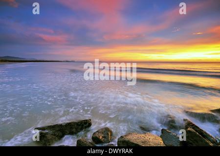 Sunset and waves at the beach in Kota Kinabalu, Sabah, Borneo, Malaysia. - Stock Photo