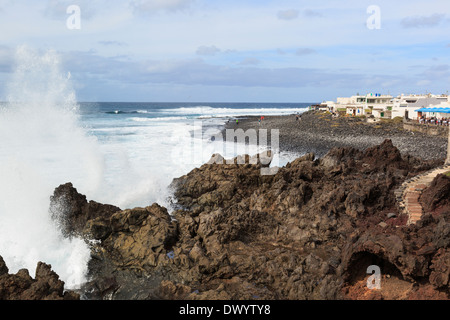 Rough seas with waves crashing on lava rocks along rugged coast at small resort of El Golfo, Lanzarote, Canary Islands, - Stock Photo