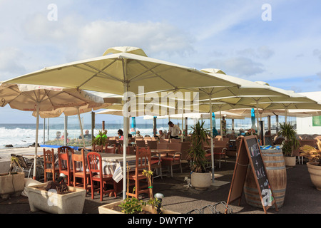 People dining under sun umbrellas in a seafront restaurant in El Golfo, Lanzarote, Canary Islands, Spain, Europe. - Stock Photo