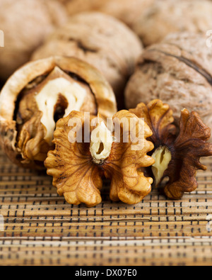 Close up vertical photo of unshelled half of walnuts lying on bamboo mat with additional nuts both shelled and unshelled - Stock Photo