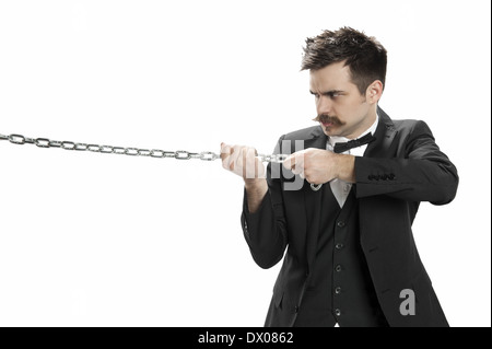Young man in business suit and bowtie scowls and pulls on a strtong chain - Stock Photo