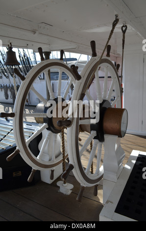 Wooden ships wheel on a British Sloop vessel. - Stock Photo