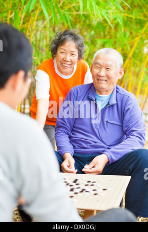 male seniors win a chinese board game .'weiqi' in the park - Stock Photo
