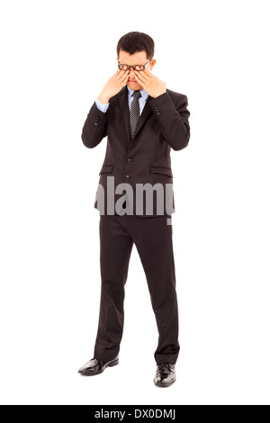 tired young businessman rubbing his eyes over white background - Stock Photo