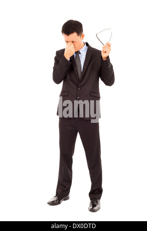 young businessman rubbing his eyes and holding glasses over white background - Stock Photo