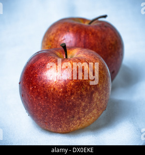 Two red apples against textured blue and white background. Square format photography. - Stock Photo