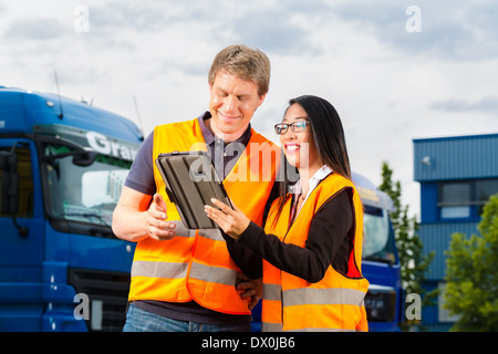Logistics - proud driver or forwarder and female coworker with tablet computer, in front of trucks and trailers - Stock Photo