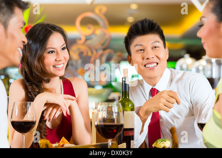 Four Asian Chinese business people having dinner in elegant club restaurant or hotel - Stock Photo