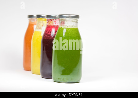 Four freshly squeezed juices in glass bottles. - Stock Photo