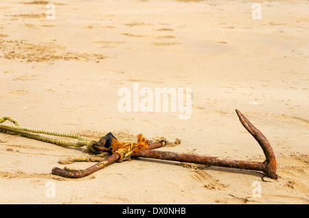 Old rusted anchor buried in sand - Stock Photo