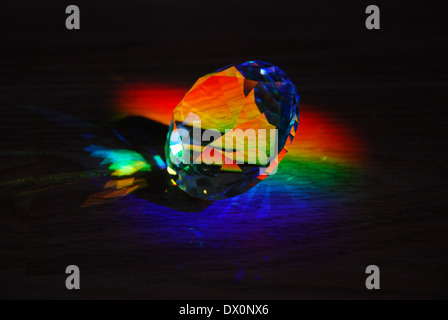 Prism casting rainbows against dark background - Stock Photo