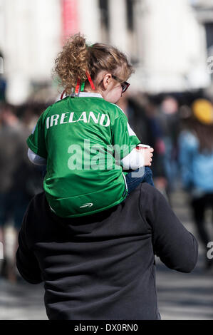 London, UK. 16 March 2014. A young girl wearing an Irish T shirt is carried on her father's shoulders during the - Stock Photo