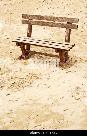 Empty wooden bench on the beach in cloudy weather. Concept of loneliness, emptiness, solitude. - Stock Photo