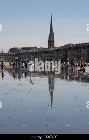 Reflections of people in Bordeaux, France having fun walking on the water in the Miroir d'eau, Mirror of Water - Stock Photo