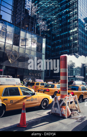 Steam pipe vent stack and yellow cab at roadworks New York City. - Stock Photo