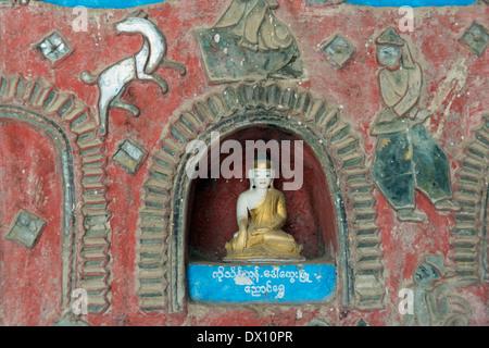 Close-up of small Buddha figure and leaded glass dog, Shwe Yaunghwe Kyaung Monastery, Nyaungshwe, Inle Lake, Myanmar - Stock Photo