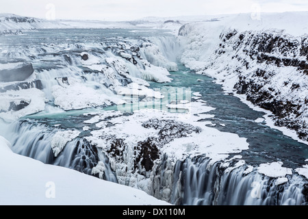 Majestic Gullfoss waterfalls form a half frozen triangle as the Hvita River falls into a wintry gorge in Western - Stock Photo