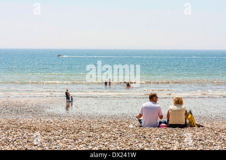 Couple sitting on the beach in the summer - Stock Photo
