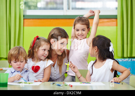 Children listen to their nursery school teacher reading a story at ...