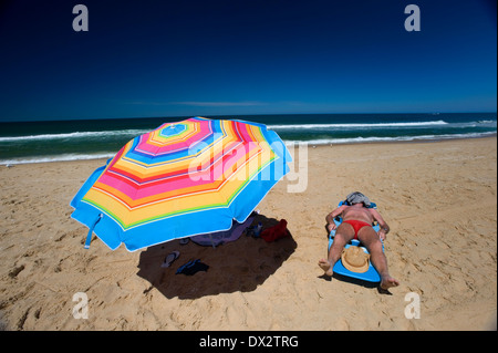 man sun baking beach umbrella rainbow - Stock Photo