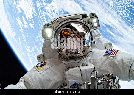 NASA astronaut Mike Hopkins takes a selfie with the Earth as background as he takes part in a spacewalks to change - Stock Photo