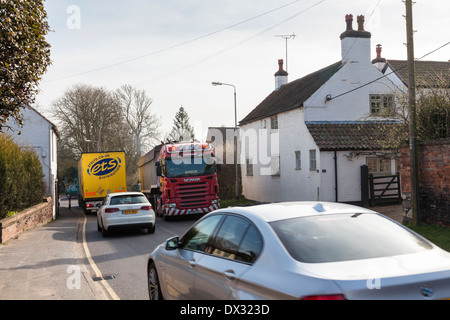 Heavy traffic passing by a house on a busy road in the small rural village of Rempstone, Nottinghamshire, England, - Stock Photo