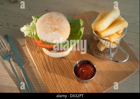 Burger with a salad garnish in a white bread bun with a side order of French fries and tomato ketchup served on - Stock Photo