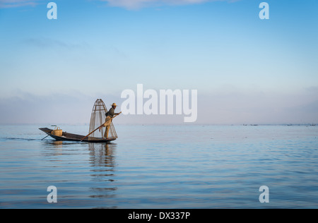 INLE LAKE, MYANMAR - CIRCA DECEMBER 2013: Fisherman rowing a typical boat in the Inle Lake, Myanmar - Stock Photo