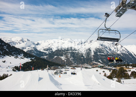 Chair lifts in Soldeu, Andorra winter sports resort. Skiers sitting on a chair lift hovering over the slope style - Stock Photo