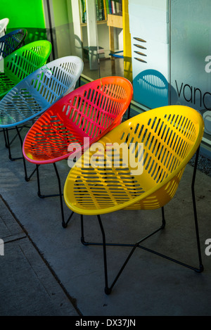 colorful round plastic chairs in a row - Stock Photo