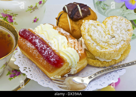 Traditional afternoon tea with cream cakes and vintage tea set. - Stock Photo