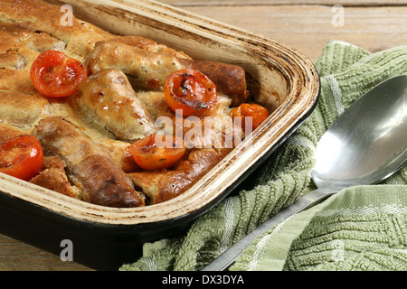 dish of home made toad in the hole sausage batter - Stock Photo