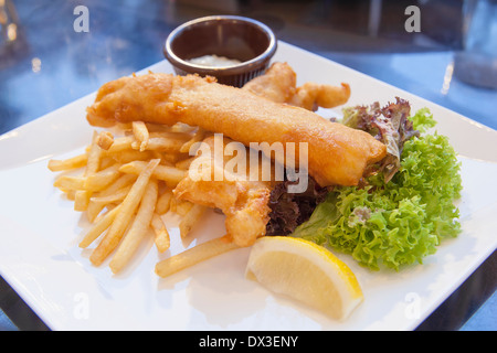Fish and Chips Over Lettuce Salad Lemon Wedge with Tartar Sauce Closeup - Stock Photo