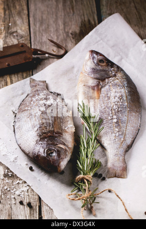 Tow raw fish bream with rosemary and sea salt server on white paper over old wooden table. - Stock Photo