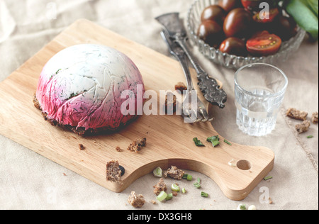 Delicious snack salad herring under a fur coat on wooden board with fork and russian vodka - Stock Photo