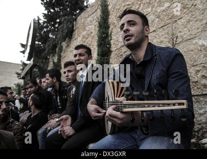 Ramallah, Palestinian Territories. 17th Mar, 2014. Palestinian playing the Oud and singging before being let inside - Stock Photo