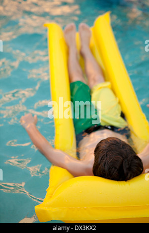 Boy laying on yellow inflatable raft in swimming pool, high angle view - Stock Photo