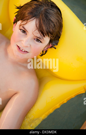 Boy with wet hair on inflatable raft in swimming pool, portrait, high angle view - Stock Photo