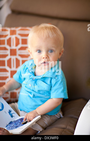 Surprised wide-eyed baby boy reading book, blonde hair, blue eyes, portrait - Stock Photo