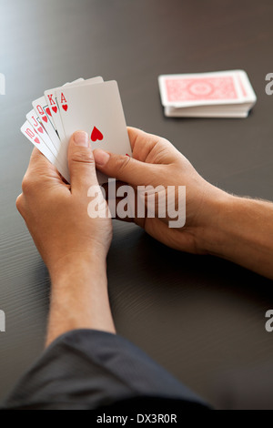 View of royal flush with hearts in hands of man playing poker with playing cards, high angle view - Stock Photo