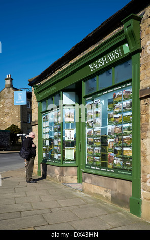 A single man looking at an estate agents window bakewell Derbyshire England uk - Stock Photo