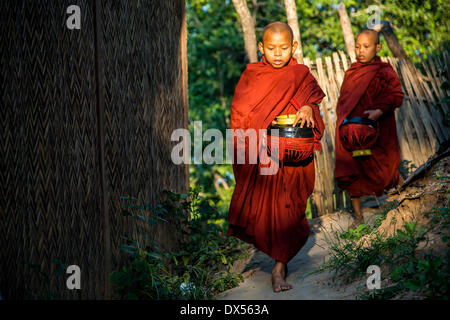 Buddhist novices with begging bowls at their morning begging tour, Mount Popa, in Bagan, Mandalay Division, Myanmar - Stock Photo